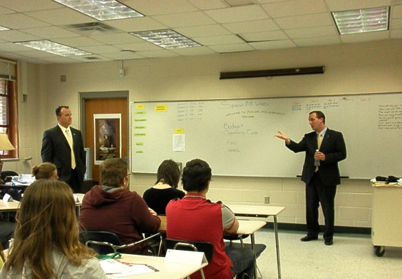 "Brian Rowe (left) and Ryan Rech, Merrill Lynch Wealth Management professionals, teach lessons in personal finance for ""JA Day."""