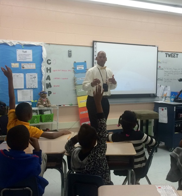 Thomas Waters discussing money management with second graders.