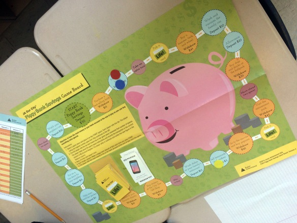 """Piggy Bank Savings Game"" game board, part of JA Our City, Junior Achievement's middle-elementary grades program."